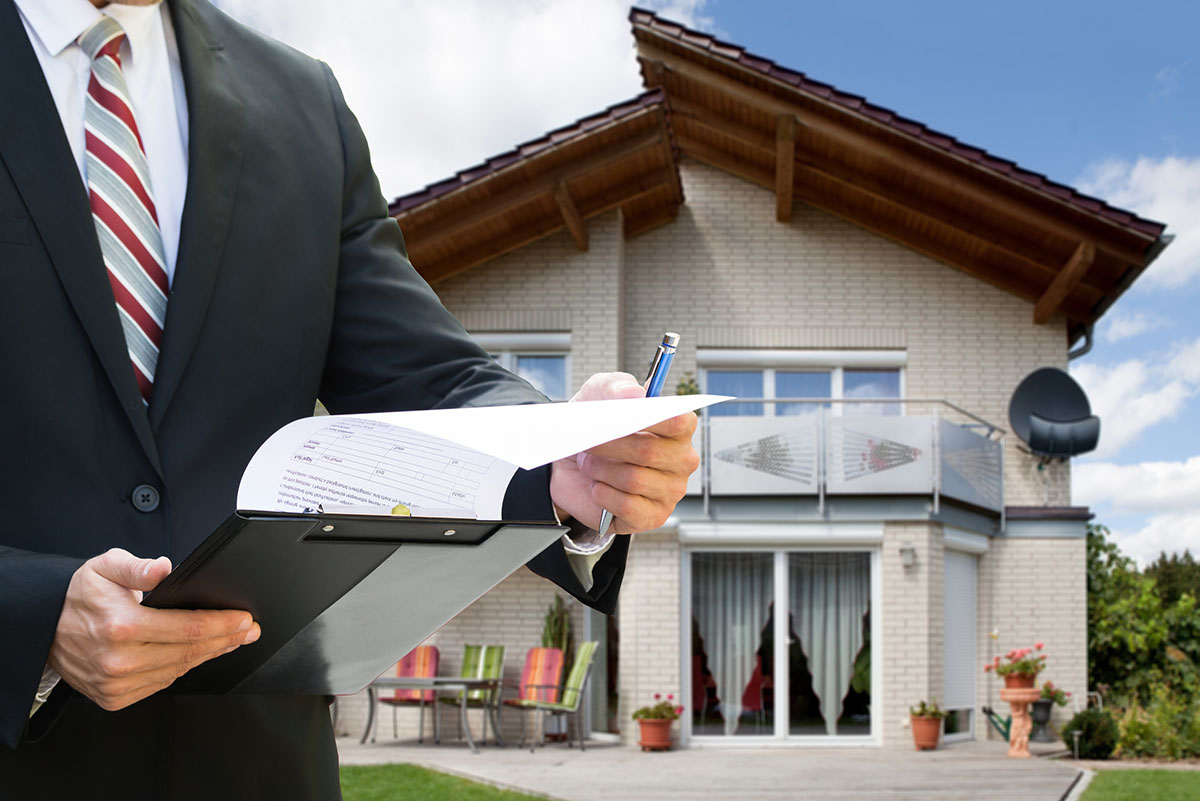 man checking documents in front of house